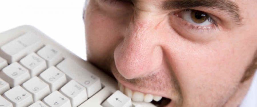 Frustrated user of computers is bitting his keyboard.